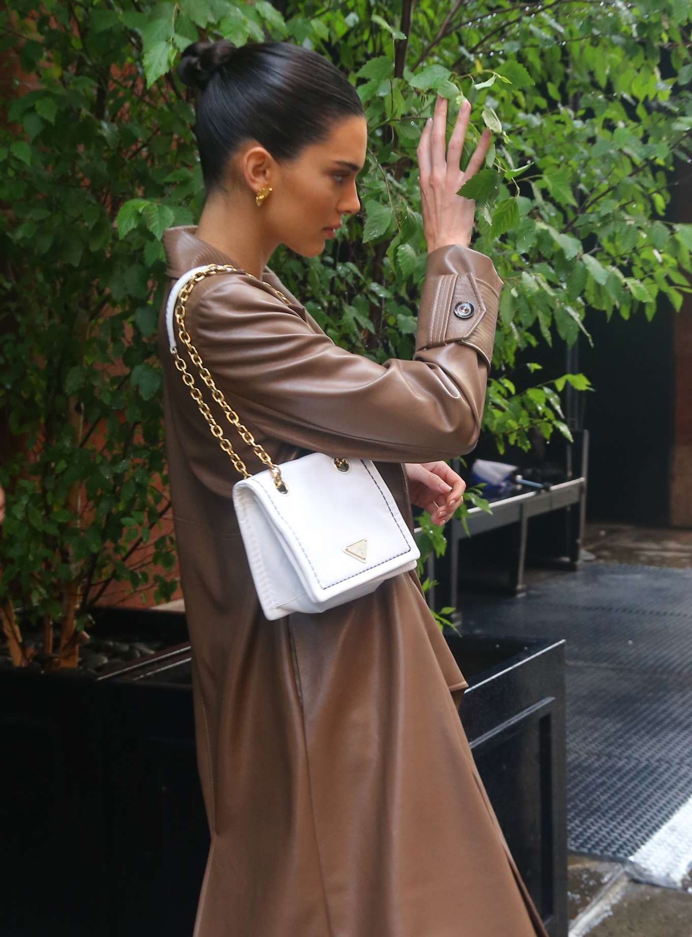 Kendall Jenner wearing a Shiny ginger brown leather two piece jacket with a leather material, full sleeves, padded shoulder, peak lapel collar, wide cuffs, wide waist belt and flared hem