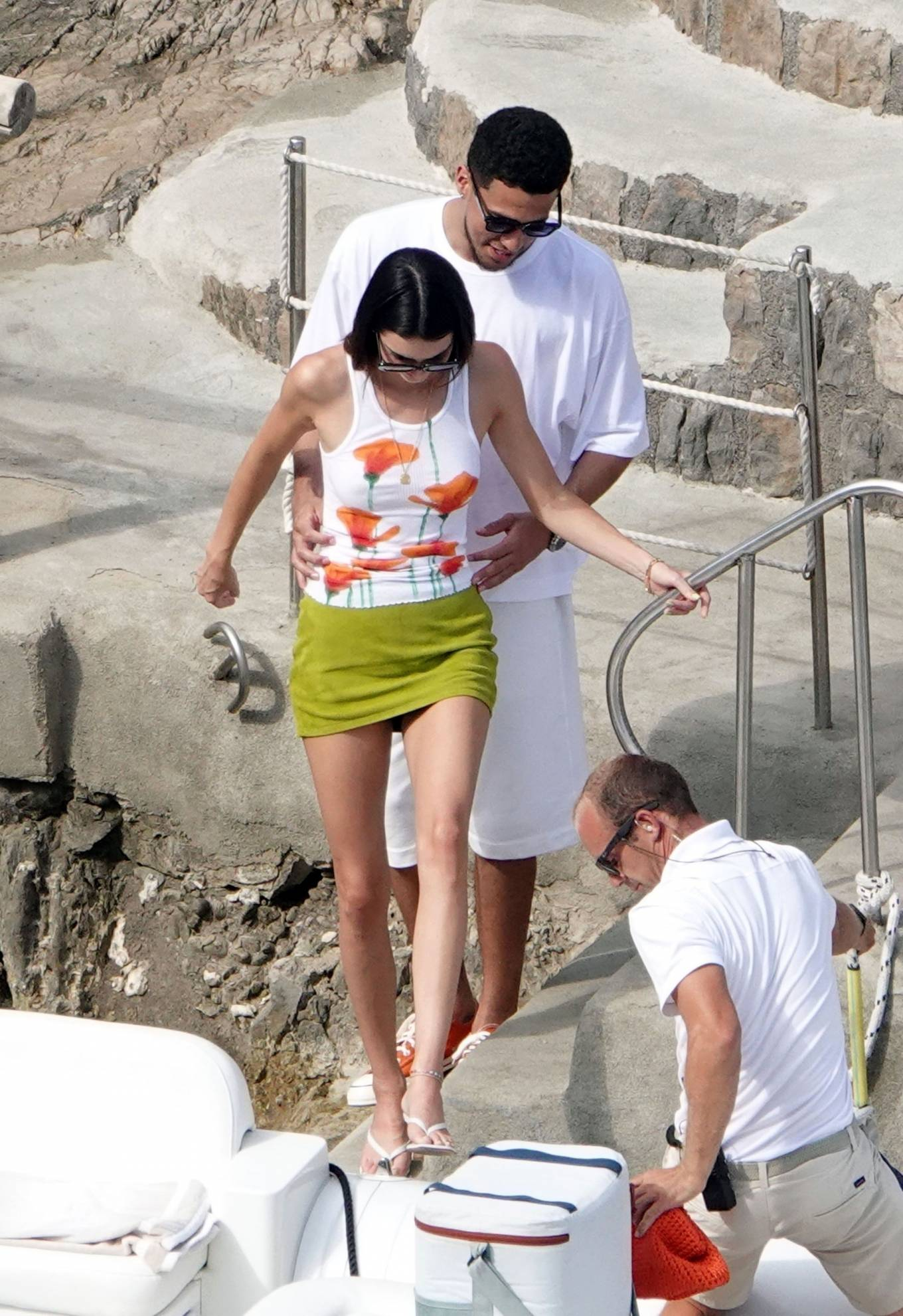 Kendall Jenner wearing a figure hugging white tank top with hand painted poppy motif and a round neck