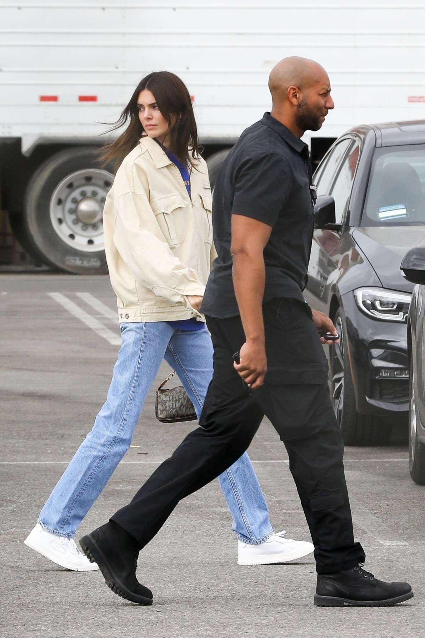 Kendall Jenner wearing side-striped white Adidas lace-up sneakers