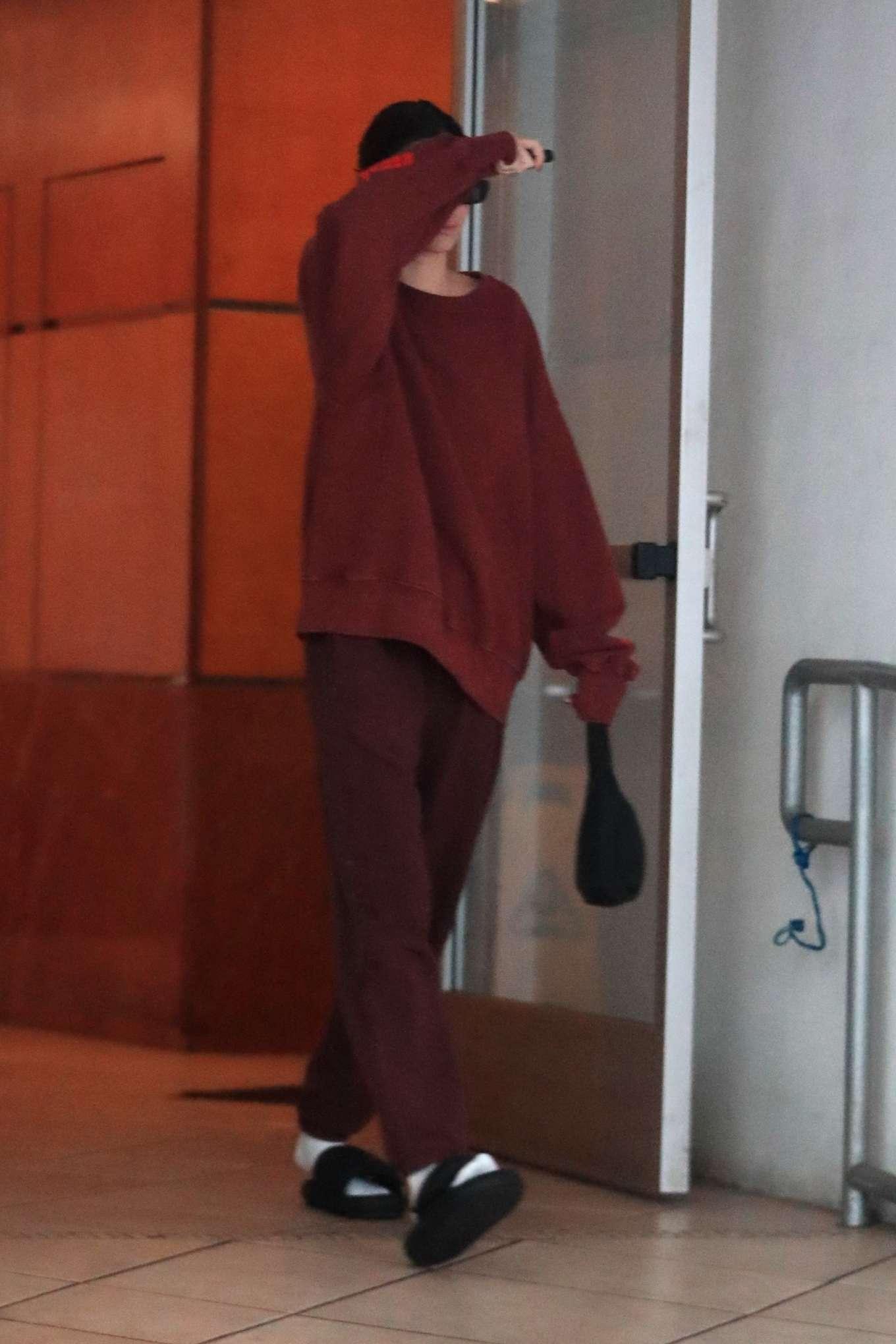 Kendall Jenner wearing black Yeezy slip on sandals with flat heel