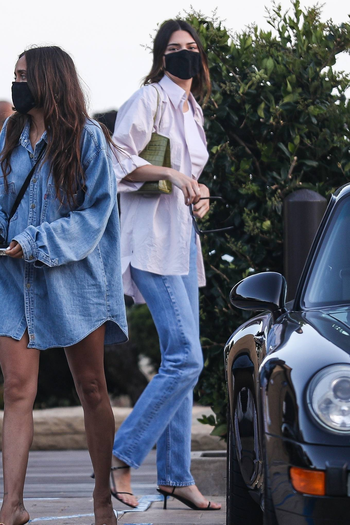 Kendall Jenner donning round black leather ankle sandals by The Row with high heel and ankle strap
