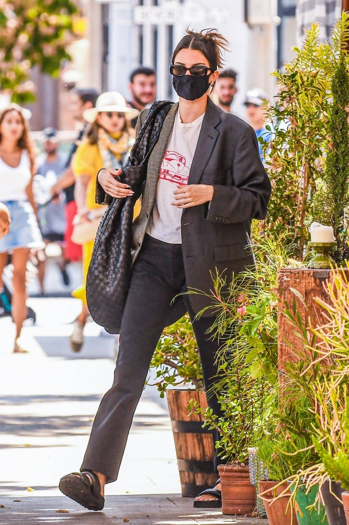 Kendall Jenner wearing round brown two-strap mules by baltini with flat heel