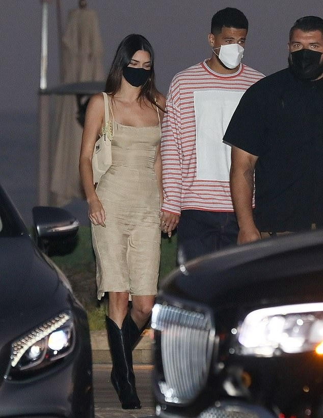 Kendall Jenner rocking narrow black leather knee high cowboy boots with kitten heel
