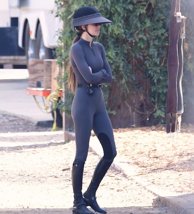 Kendall Jenner donning black leather knee high boots with flat heel