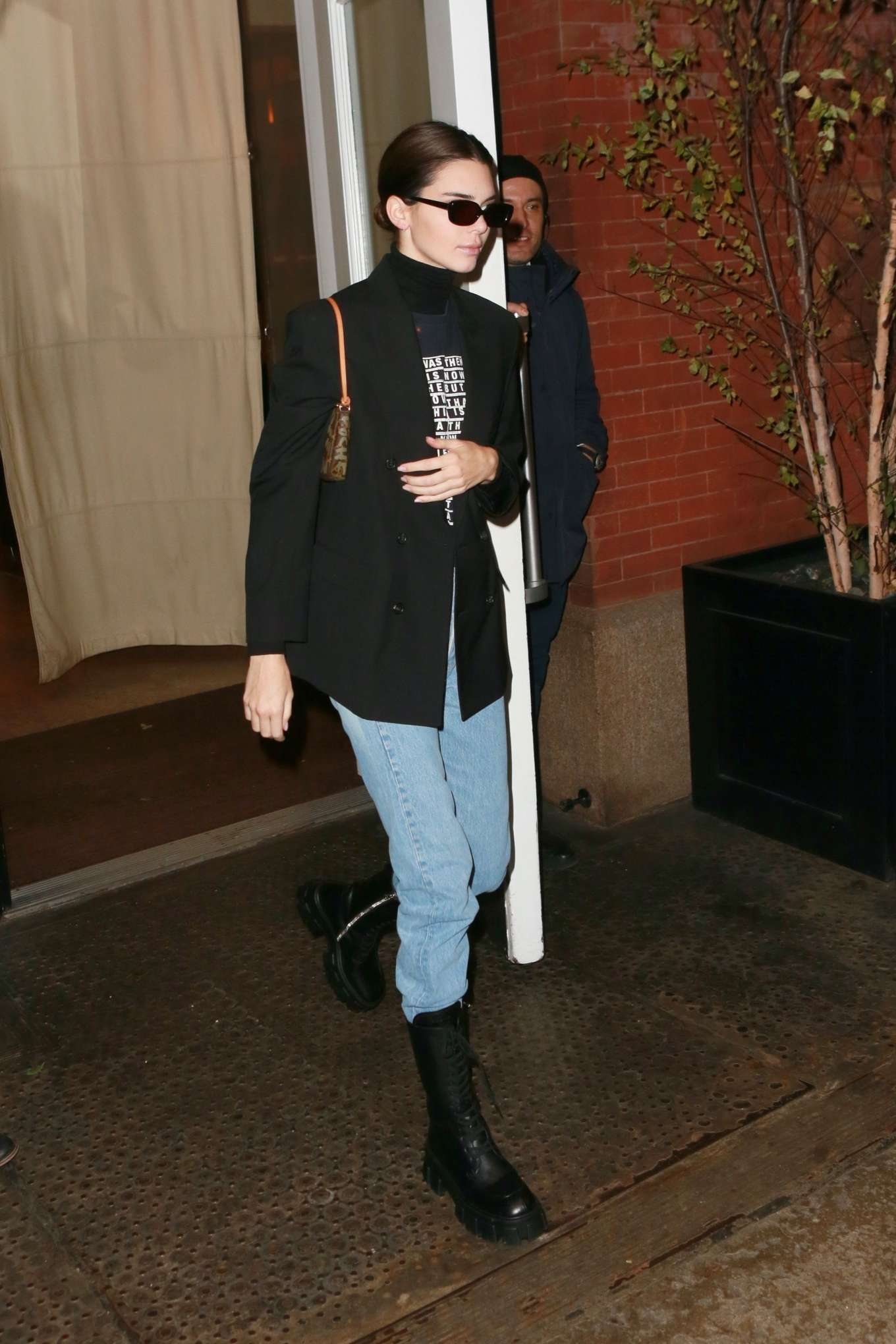 Kendall Jenner donning black leather mid calf boots with chunky sole
