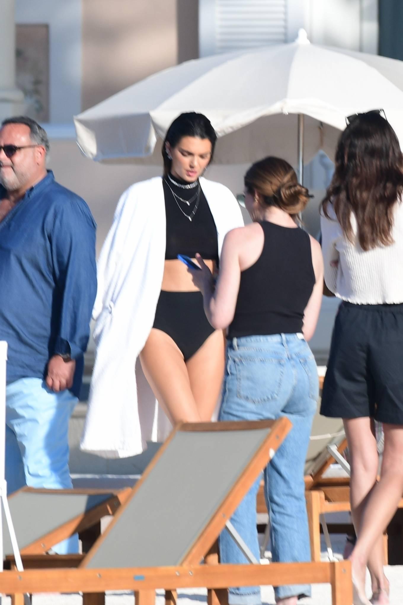 Kendall Jenner, blue jacket, black crop top, baseball collar, open front, front zip, waist length, rolled sleeves, black bikini bottom. Kendall Jenner wearing a metallic blue open front jacket with rolled sleeves and baseball collar