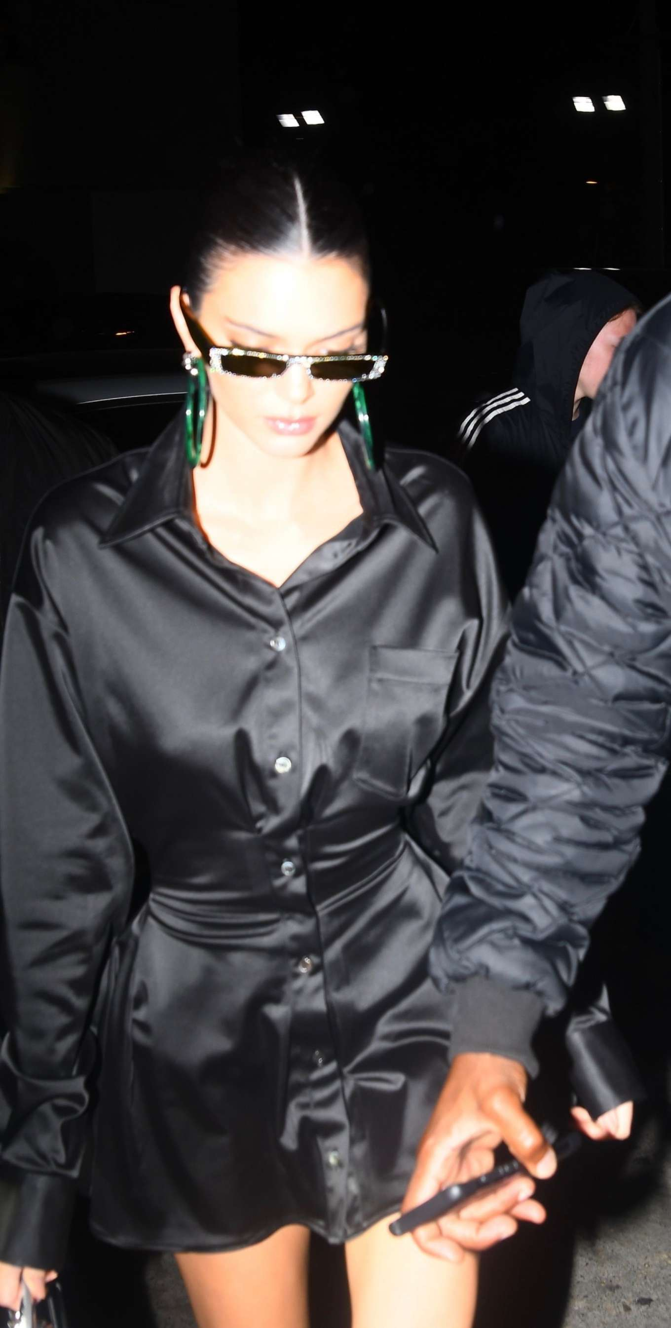 Kendall Jenner wearing a Sexy shiny black satin shirt dress with a satin fabric, extra long sleeves, drop shoulder, shirt collar, wide cuffs and pleated