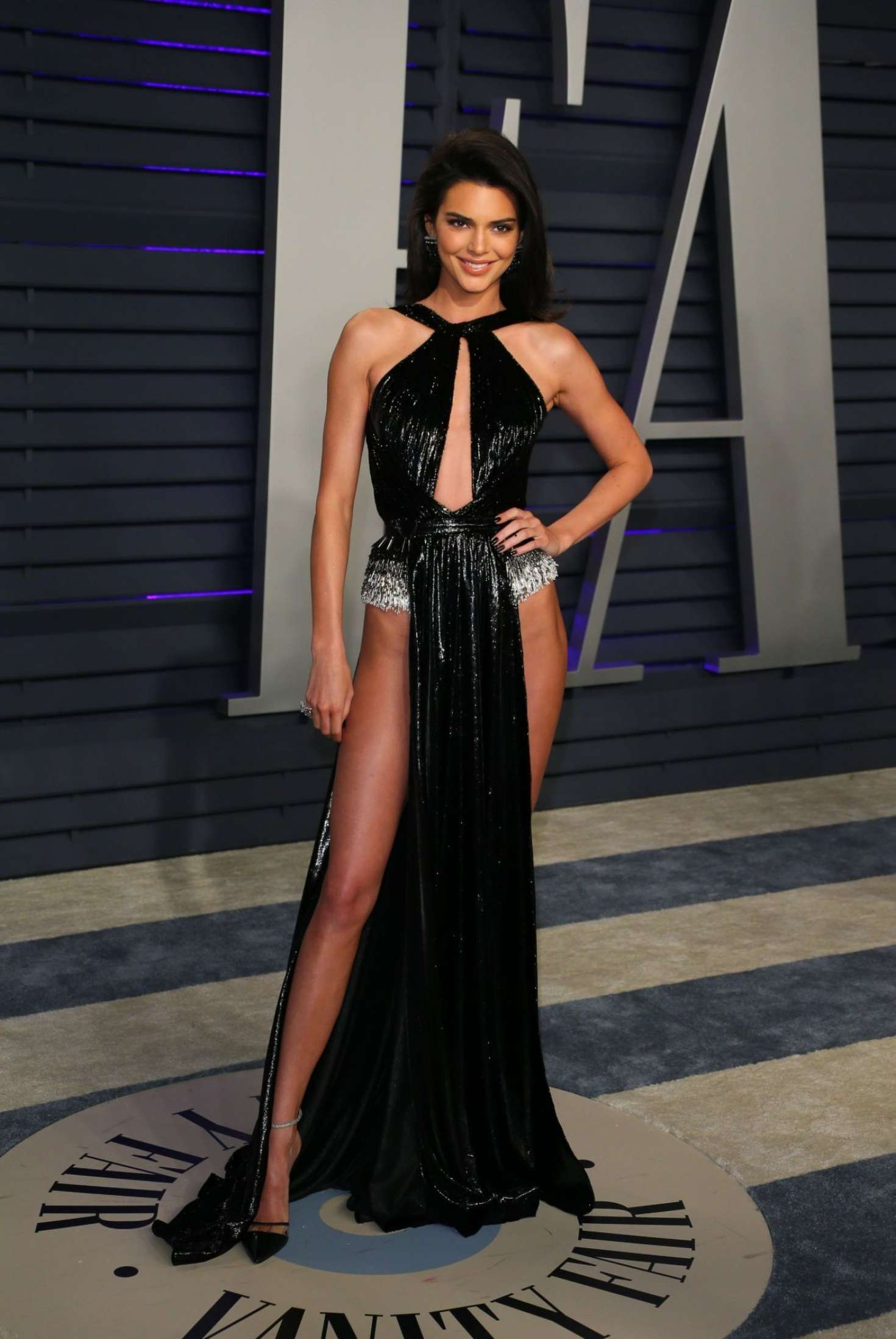 Kendall Jenner donning pointy black pumps with high heel and thin ankle strap