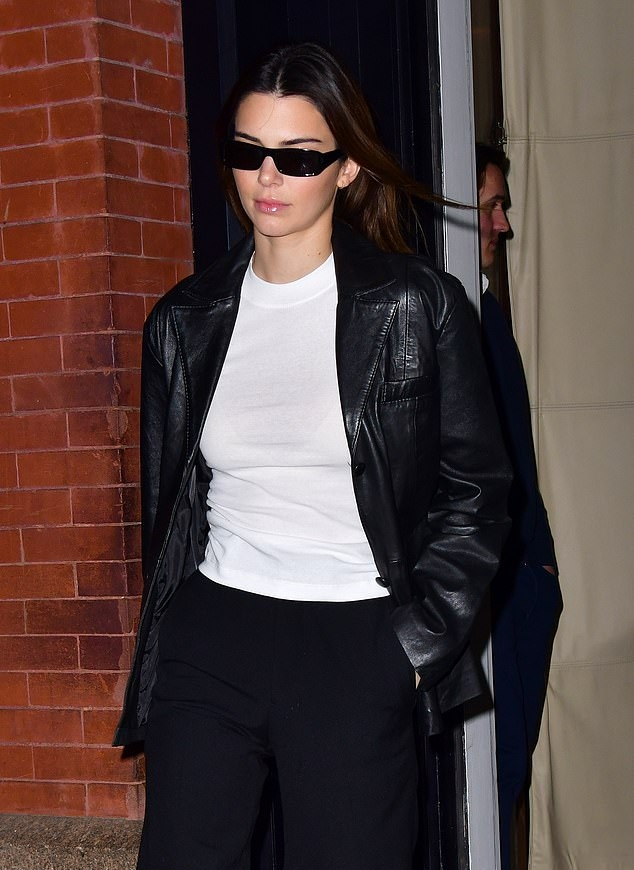 Kendall Jenner, black jacket, leather, white tee, white canvas shoes, front zip, hip length, full sleeves, peak lapel collar, relaxed fit, black pants, black Prada purse, black sunglasses. Kendall Jenner donning a relaxed fit black leather jacket with full sleeves and peak lapel collar