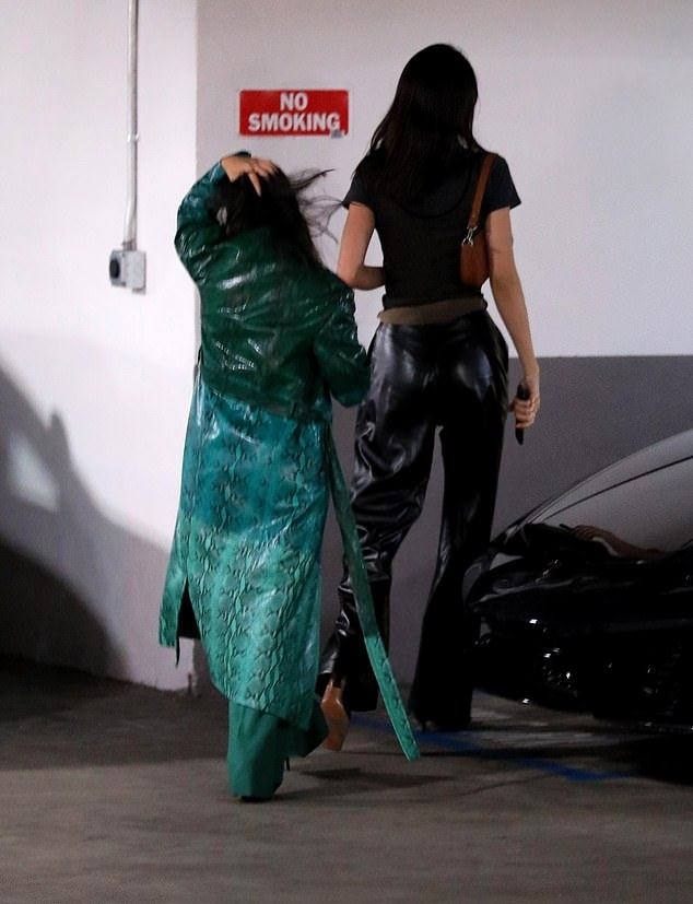 Kendall Jenner donning straight fit black leather wide cut jeans with high rise