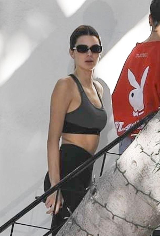 Kendall Jenner, black leggings, grey sports bra, black Velvet Canyon sunglasses, showcase, waist high, skinny, flat stomach. Kendall Jenner donning black skinny leggings