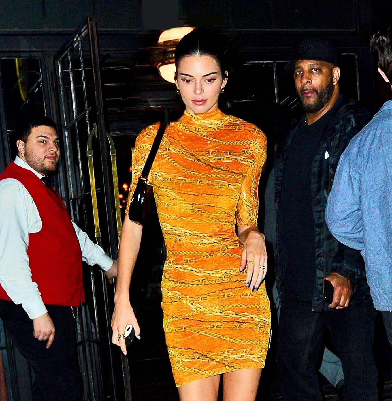 Kendall Jenner wearing a Formfitting shiny Bright yellow dress with a velvet fabric, elbow length sleeves, padded shoulder and a turtleneck