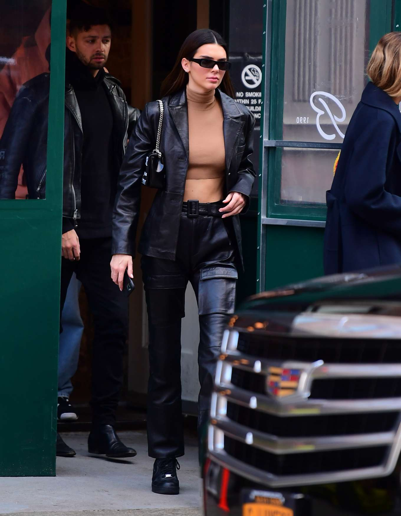 Kendall Jenner donning a matching shiny black open front leather blazer with a satin fabric, full sleeves, peak lapel collar and flap pockets