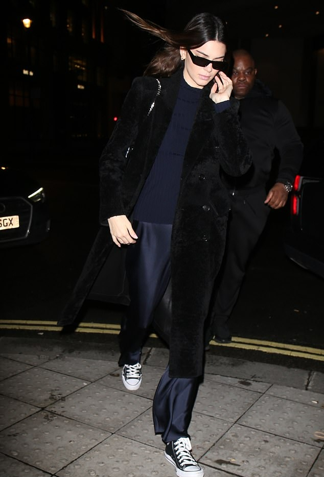 Kendall Jenner wearing a black button front Balenciaga luxe velvet trench coat with full sleeves, peak lapel collar and flap pockets