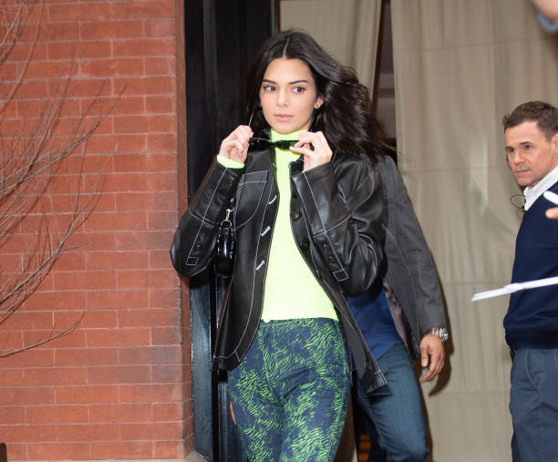 Kendall Jenner donning a Figure hugging neon green sweater with a woolen material, extra long sleeves and a turtleneck