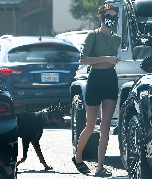 Kendall Jenner rocking black open toe sandals by Birkenstock with buckled ankle strap