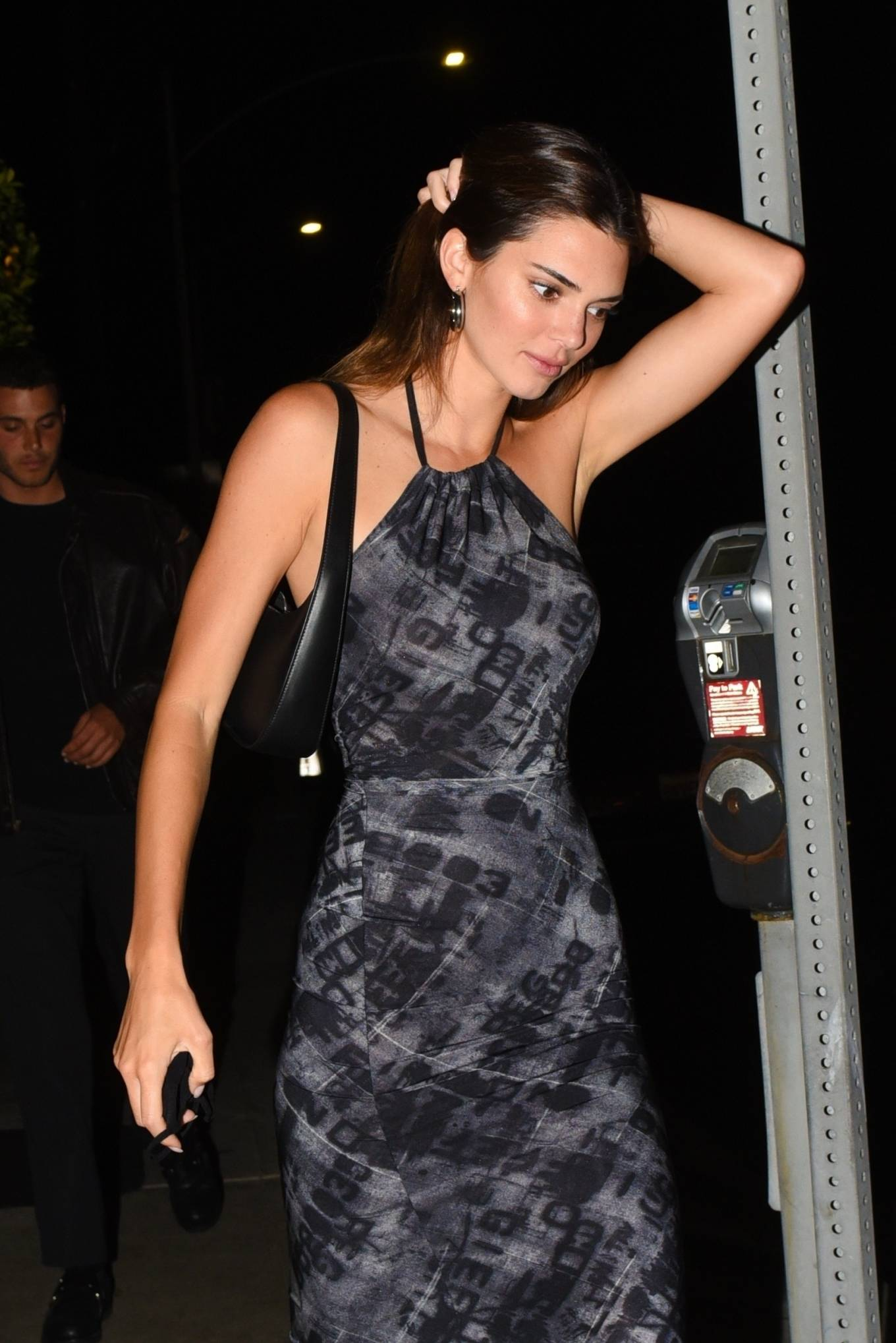 Kendall Jenner donning a Figure hugging grey tie dye printed midi dress with a halter neck and cinched waist