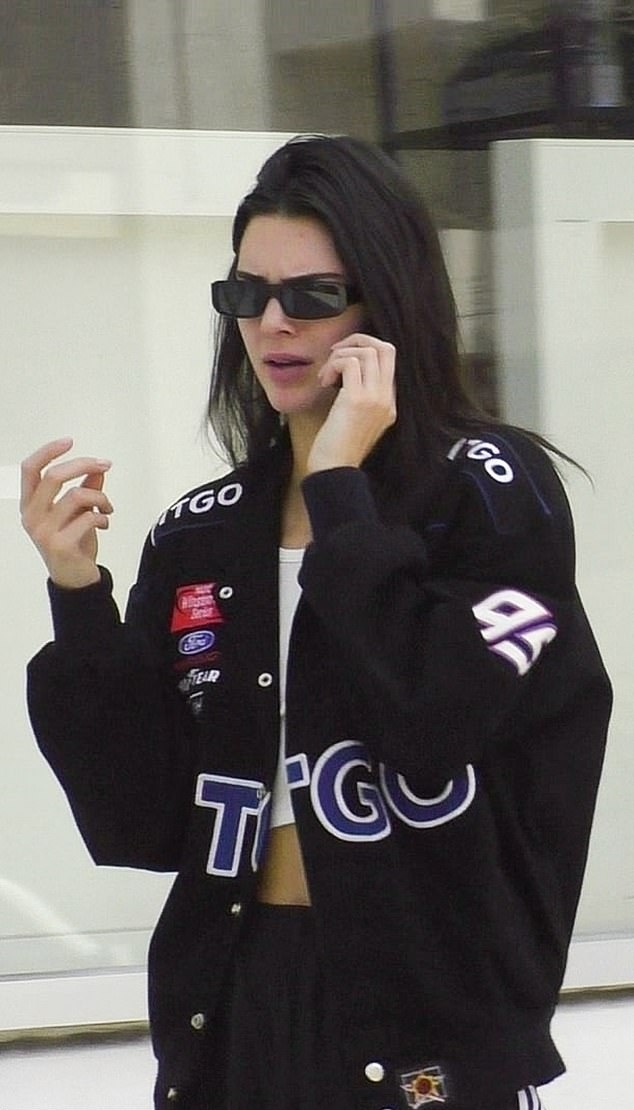 Kendall Jenner wearing chunky black Adidas sneakers with brand logo