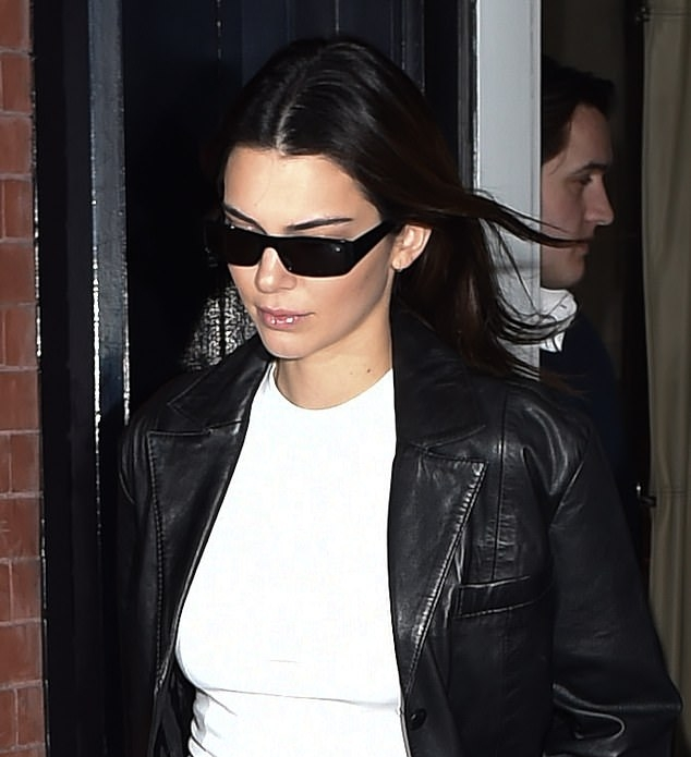 Kendall Jenner, leather, black jacket, white canvas shoes, white tee, full sleeves, peak lapel collar, relaxed fit, front zip, hip length, black Prada purse, black pants, black sunglasses. Kendall Jenner donning a relaxed fit black leather jacket with full sleeves and peak lapel collar