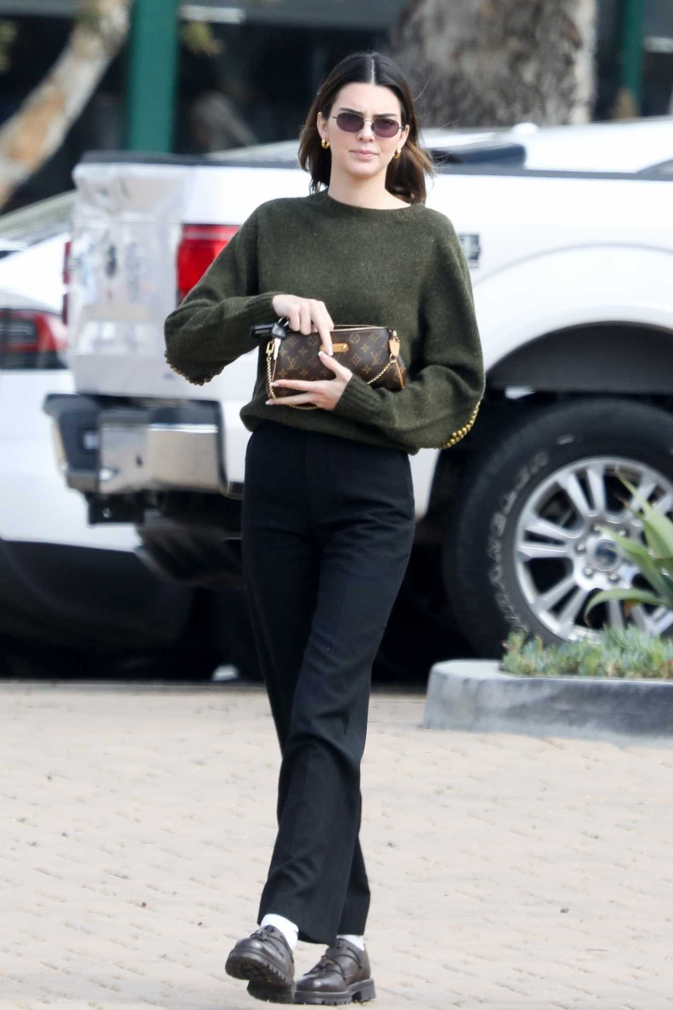 Kendall Jenner rocking a Dark bottle green woolen sweater with a woolen fabric, full sleeves, embellished and a crew neck