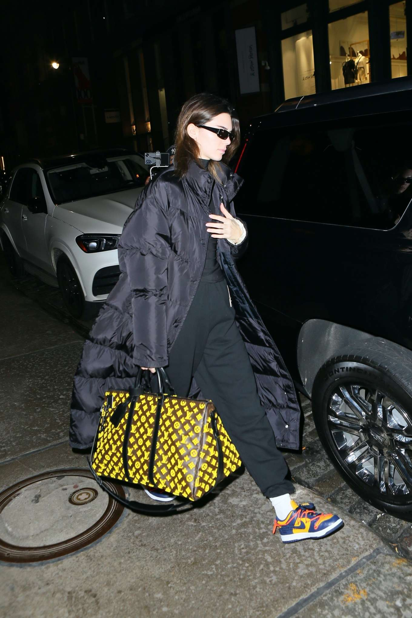 Kendall Jenner wearing a oversized black open front nylon quilted long jacket with extra long sleeves and stand-up collar