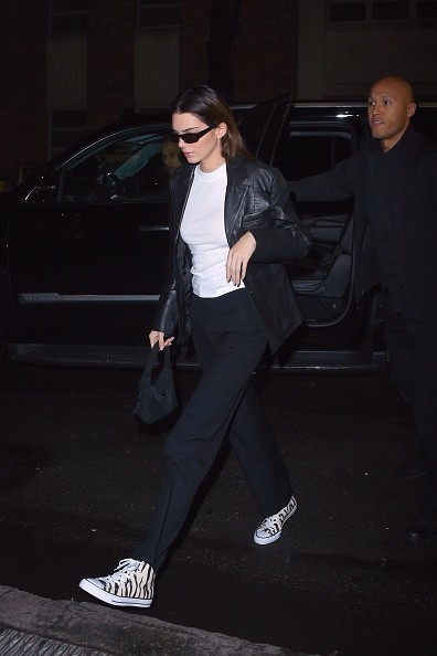 Kendall Jenner, leather, black jacket, white tee, white canvas shoes, hip length, full sleeves, peak lapel collar, relaxed fit, front zip, black pants, black Prada purse, black sunglasses. Kendall Jenner donning a relaxed fit black leather jacket with full sleeves and peak lapel collar
