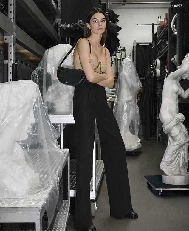 Kendall Jenner donning straight fit black button front trousers with high waist