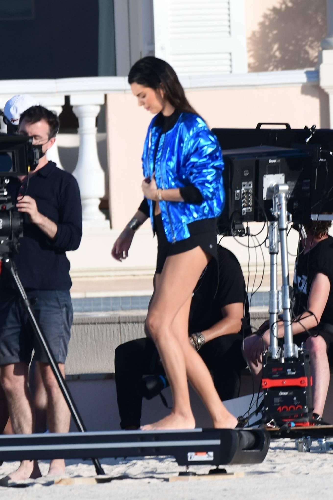 Kendall Jenner, blue jacket, black crop top, waist length, rolled sleeves, baseball collar, open front, front zip, black bikini bottom. Kendall Jenner wearing a metallic blue open front jacket with rolled sleeves and baseball collar