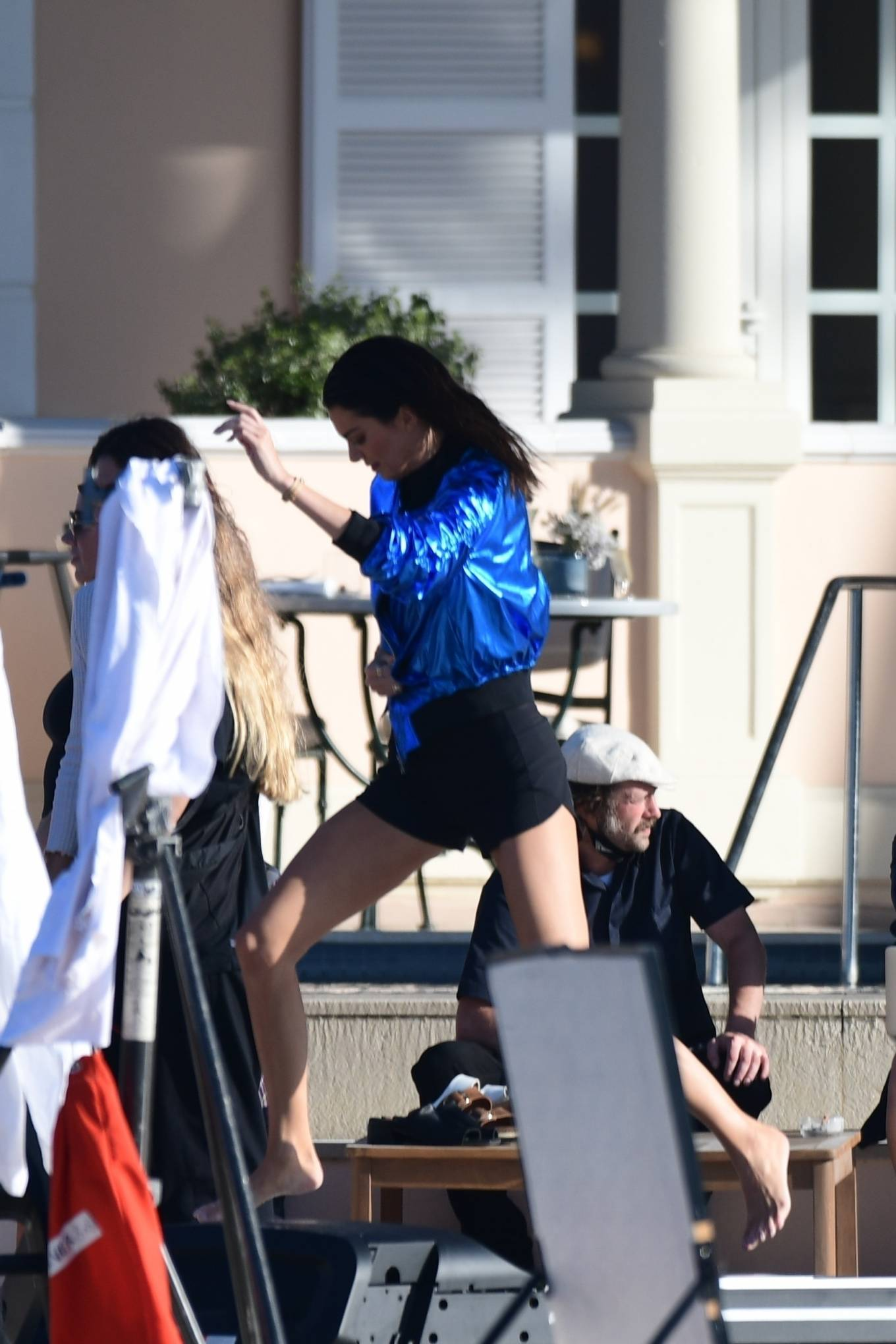 Kendall Jenner wearing a metallic blue open front jacket with rolled sleeves and baseball collar