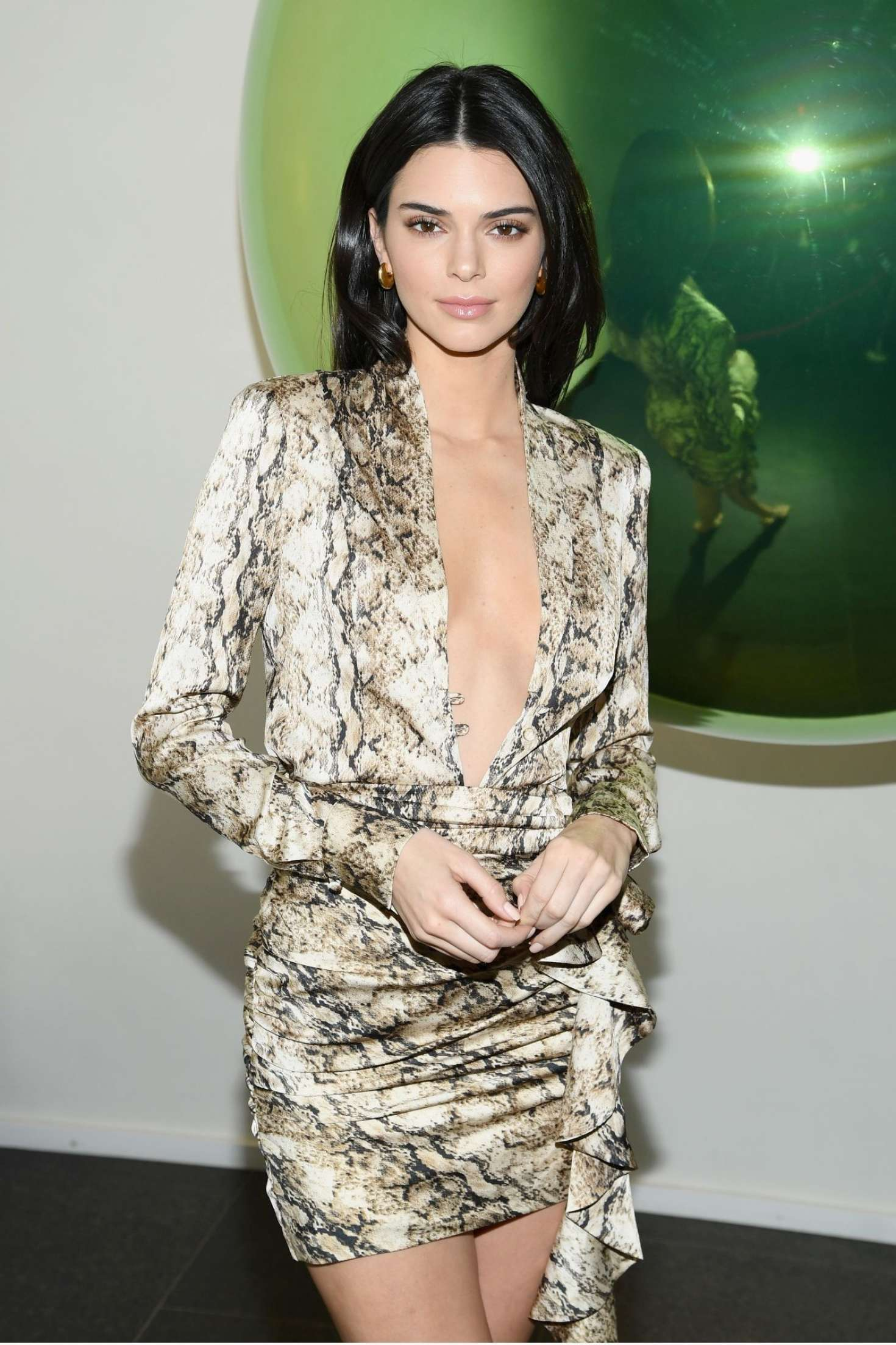 Kendall Jenner donning a shiny brown satin blouse with a snakeskin fabric, long sleeves and plunging neckline that almost went down to her waist