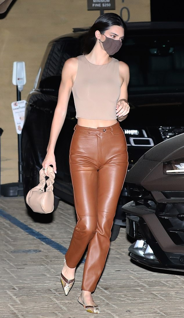 Kendall Jenner wearing straight fit brown leather high rise trousers while heading to grab dinner in Malibu