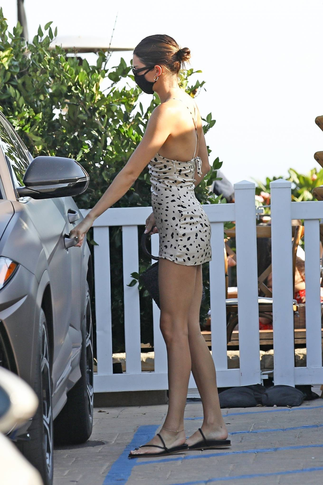Kendall Jenner donning a figure hugging cream dress with a scoop neck and spaghetti straps