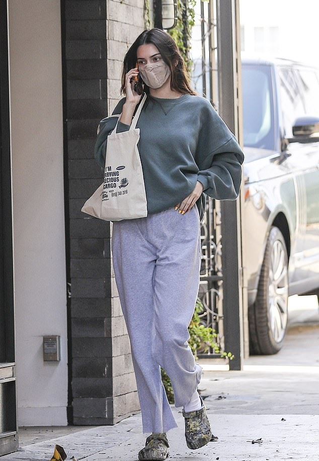 Kendall Jenner wearing round multicolor slip on slippers by crocs