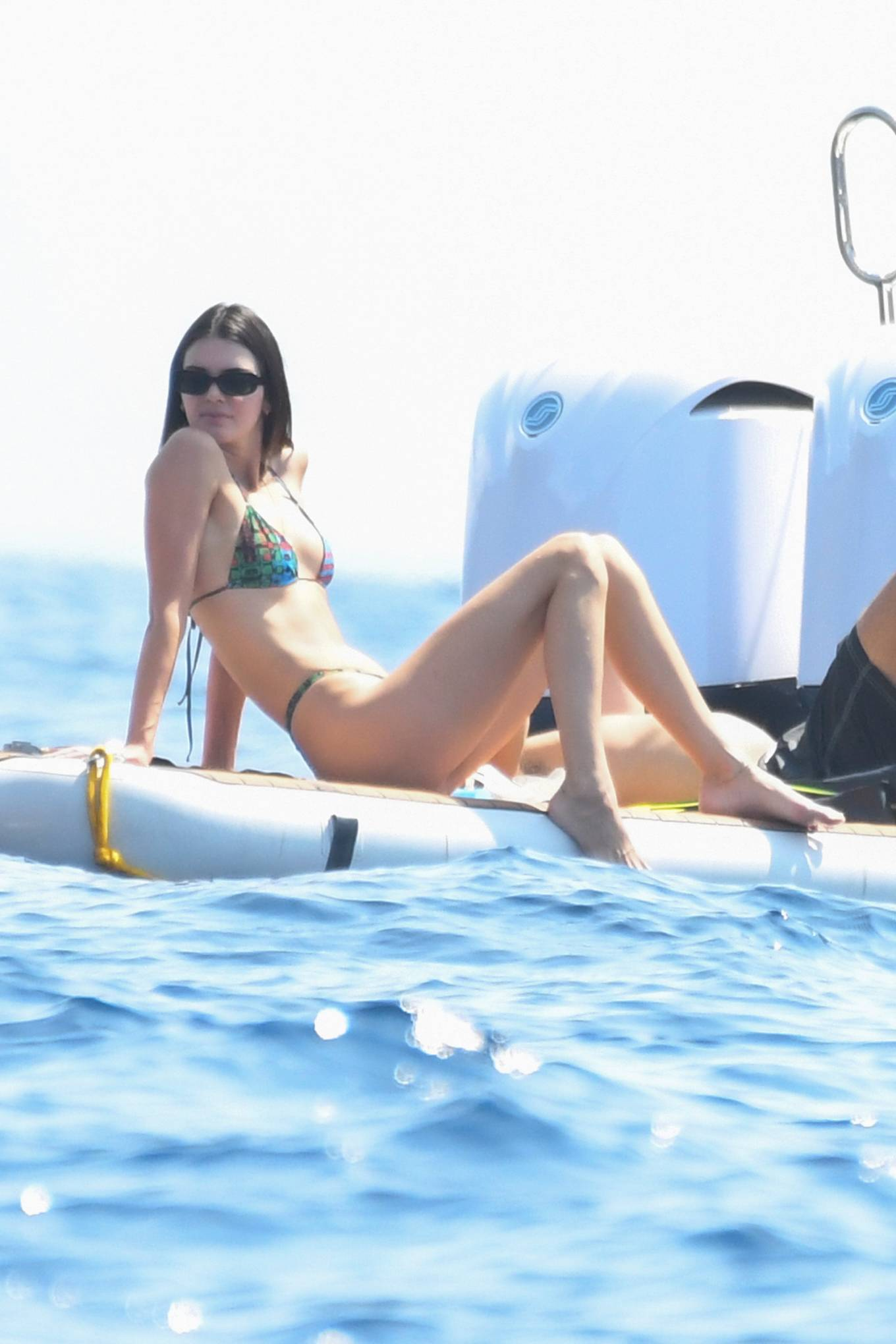 Kendall Jenner, black Gentle Monster sunglasses, showcase, patterned print, tiny, straps, deep neck, triangle, flat stomach, straps tied at the shoulder, halter neck, figure hugging, spaghetti straps. Kendall Jenner wearing a figure hugging plunging bikini top with a halter neck and two ties at the shoulder
