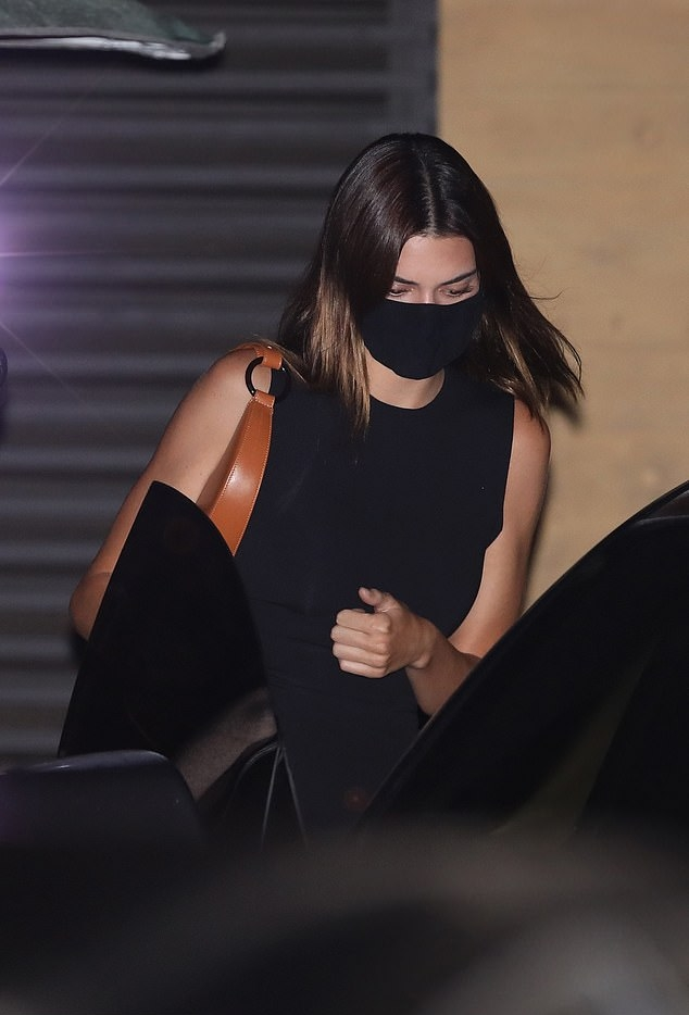 Kendall Jenner wearing a figure hugging black tank top with a crew neck