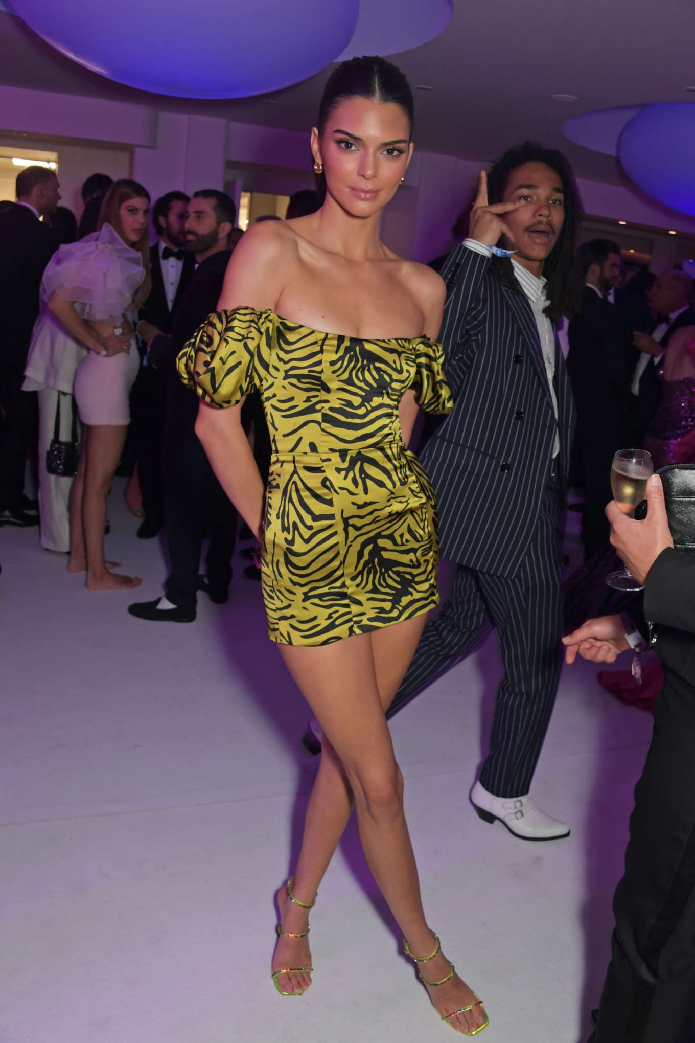 Kendall Jenner donning strappy gold yellow open toe sandals with high heel and thin straps