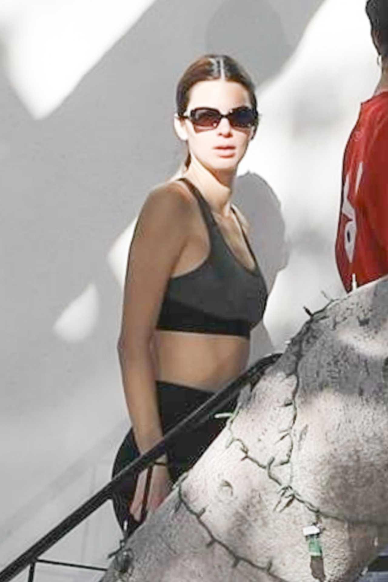 Kendall Jenner, black leggings, grey sports bra, black Velvet Canyon sunglasses, waist high, skinny, showcase, flat stomach. Kendall Jenner donning black skinny leggings