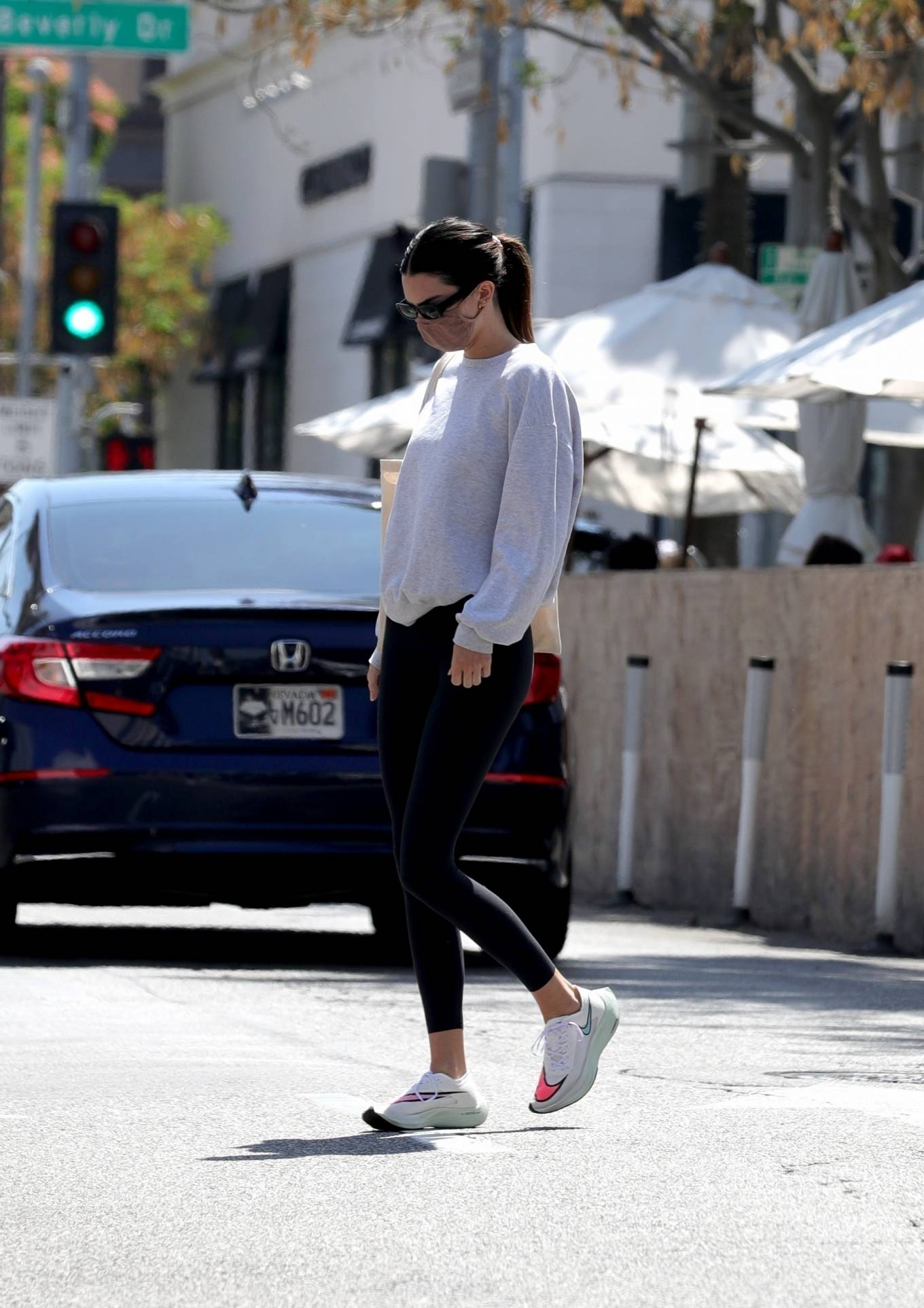 Kendall Jenner donning brand logo white Nike lace-up sneakers