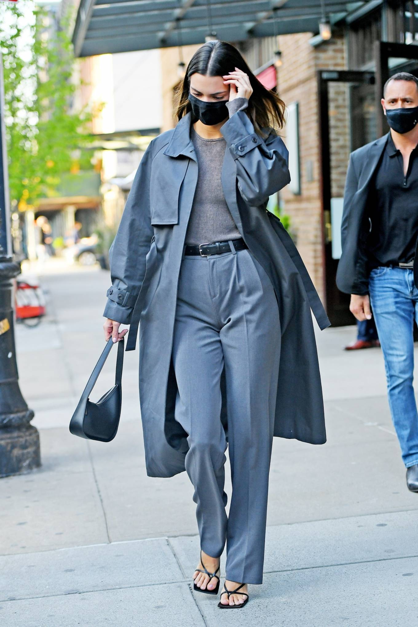 Kendall Jenner donning straight fit grey spandex pleated trousers with high waist with side pockets and a cotton material