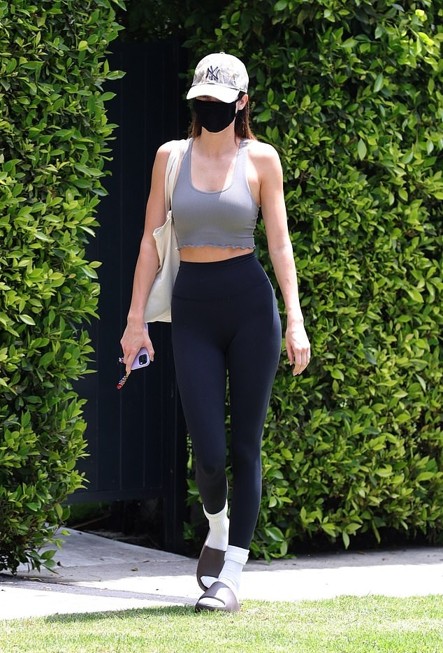 Kendall Jenner rocking skinny black high rise workout leggings with a stretch fabric material