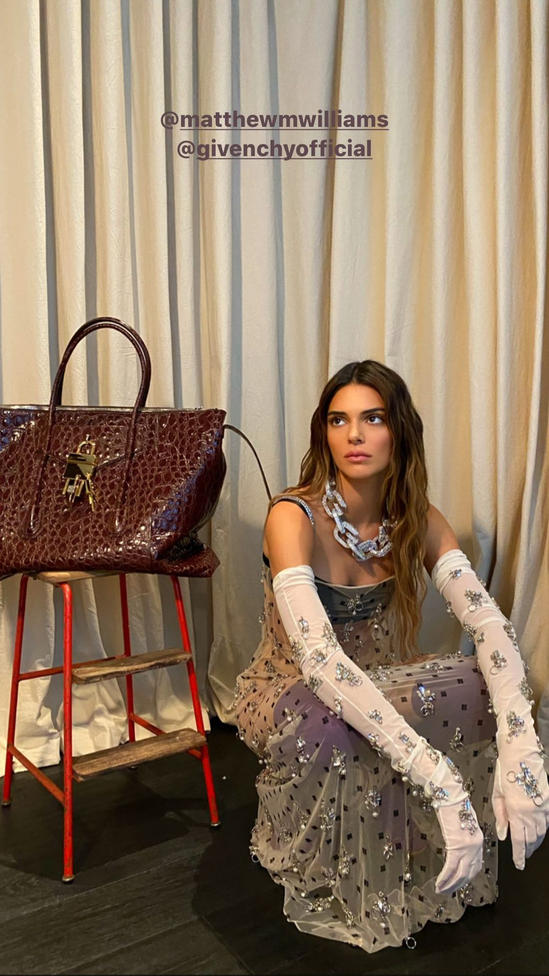 Kendall Jenner, ivory maxi dress, see-through, maroon purse, tease at, sexy, thin shoulder strap, low neck, flowing, sequin detailing. Kendall Jenner donning a sheer ivory dress with a sequin detailing material and thin shoulder strap