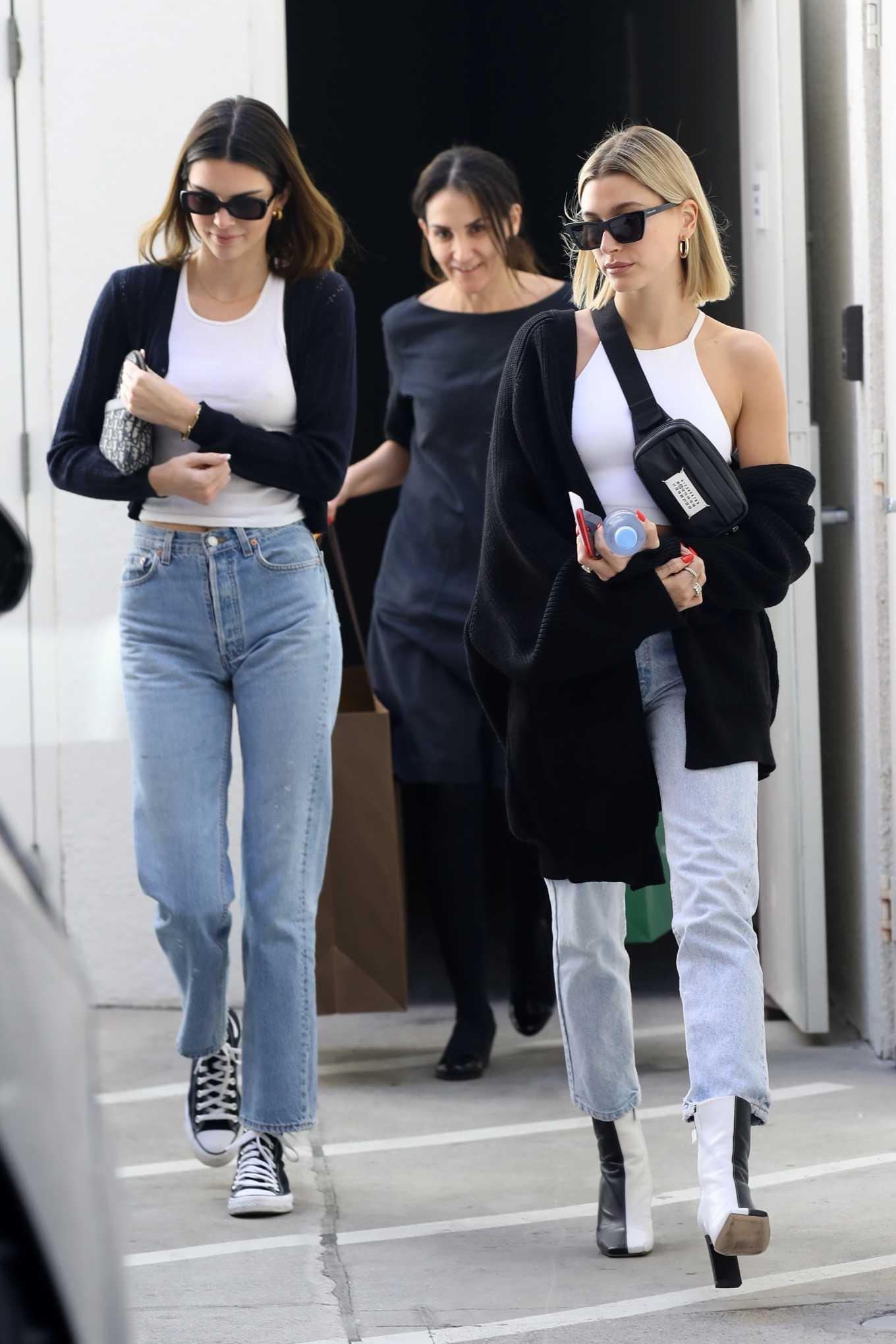 Kendall Jenner, light blue jeans, denim, black crop jacket, black canvas shoes, waist high, straight fit, braless white tank top, black Dior purse. Kendall Jenner rocking straight fit light blue denim jeans