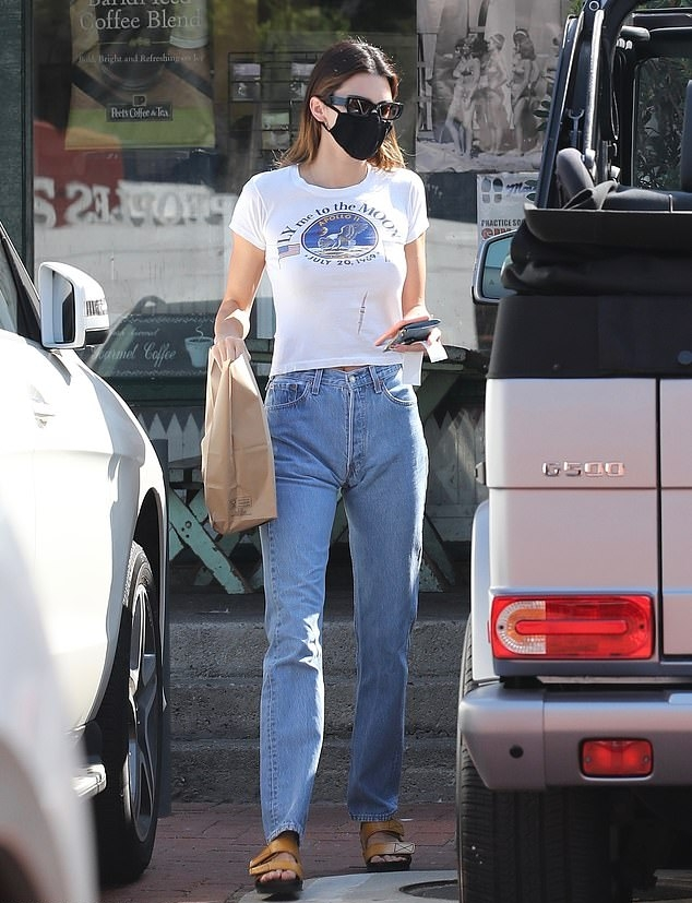 Kendall Jenner donning a white graphic print graphic tee with short sleeves and a crew neck
