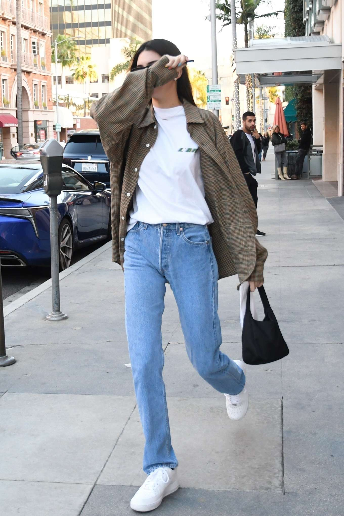 Kendall Jenner wearing white leather lace-up sneakers