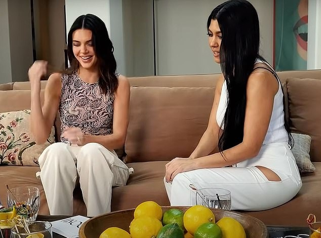 Kendall Jenner wearing straight fit beige pleated trousers with high waist