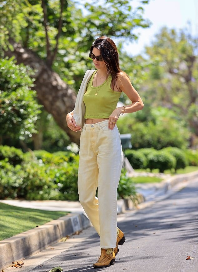 Kendall Jenner, yellow boots, lime green crop top, white The Row shoulder bag, pattern, tapered toe, lace-up, yellow cowboy boots, beige Source Unknown jeans, black sunglasses. Kendall Jenner donning pattern yellow lace-up cowboy boots