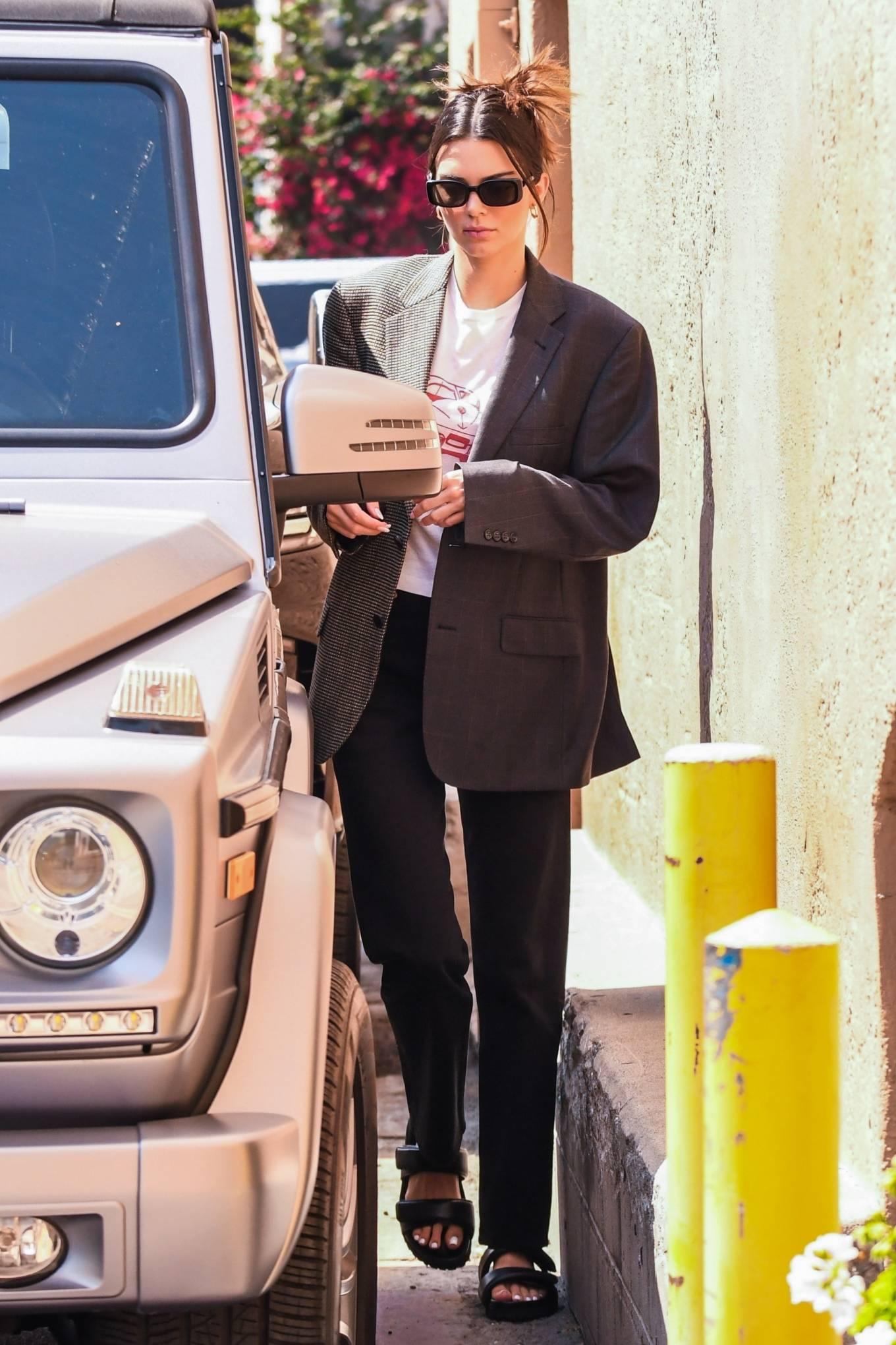 Kendall Jenner, brown mules, baltini mules, oversized metallic grey blazer, black Bottega Veneta shoulder bag, round, two-strap, flat heel, white top, black sunglasses, grey pants. Kendall Jenner rocking round brown two-strap mules by baltini with flat heel