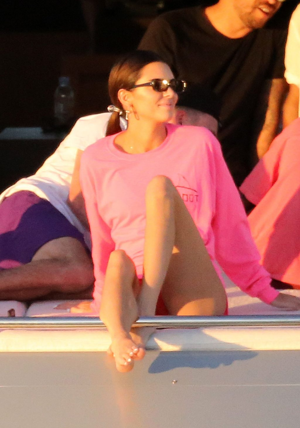 Kendall Jenner wearing a oversized neon pink sweatshirt with extra long sleeves, a round neck and ribbed trim hem