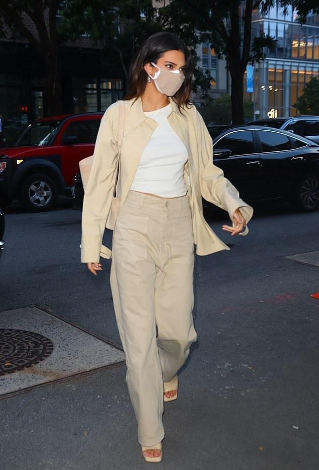 Kendall Jenner donning a oversized off white denim shirt with long sleeves and shirt collar