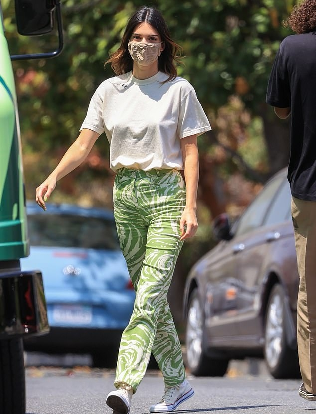 Kendall Jenner donning a relaxed fit off white top with half sleeves and a crew neck